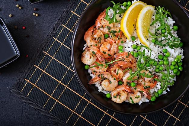 Arroz con guisantes verdes jóvenes, camarones y rúcula en un tazón negro. comida sana. tazón de buda. vista superior. lay flat Foto gratis