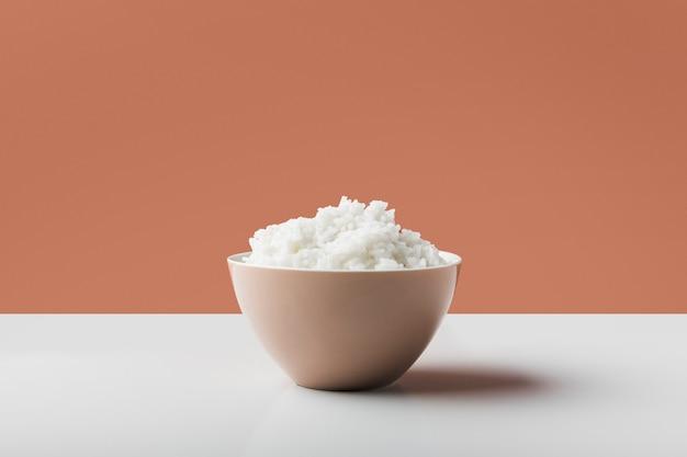 Arroz hervido blanco cocido en el cuenco en la tabla blanca contra fondo marrón Foto gratis
