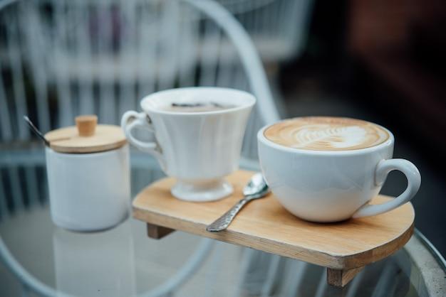 Arte caliente del latte en taza de café en la tabla de madera en cafetería Foto gratis