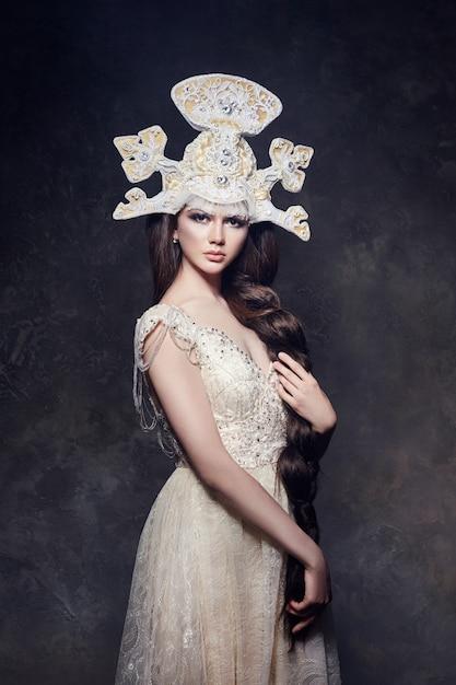 Arte mujer con larga trenza en lujoso vestido largo. Foto Premium