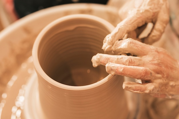 La artesana da forma a la olla de barro con las manos en la rueda de alfarería. Foto gratis
