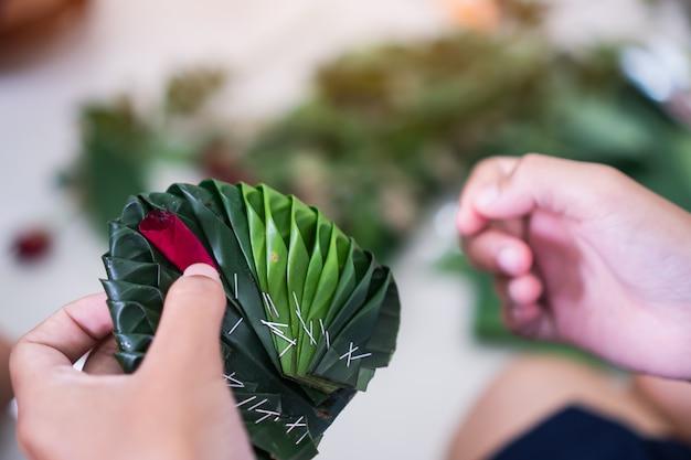 Artesanías, los estudiantes tailandeses están aprendiendo a hacer hojas de plátano verde adornadas con flores. Foto Premium