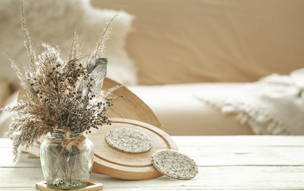 Artículos decorativos en el acogedor interior de la habitación, un jarrón con flores secas sobre una mesa de madera clara. Foto gratis