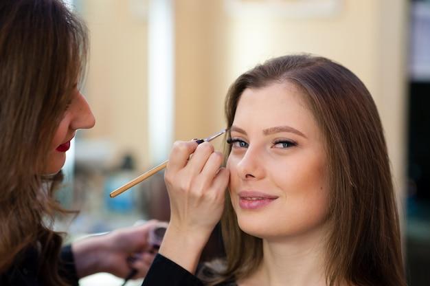 Artista de maquillaje hace cambio de imagen hermosa chica Foto Premium