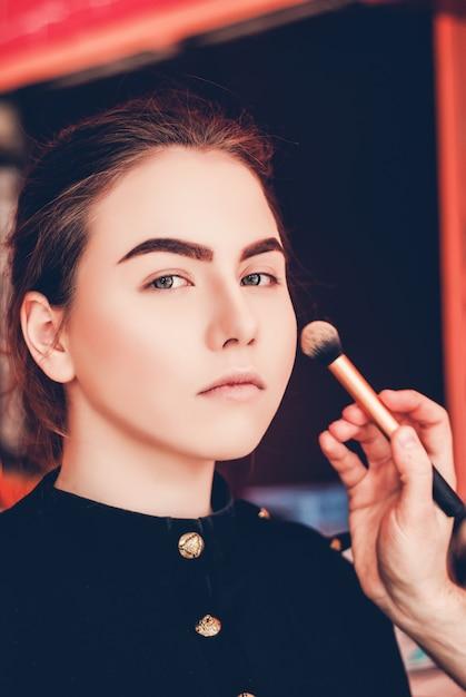Artista de maquillaje haciendo maquillaje de una hermosa joven en el estudio Foto Premium