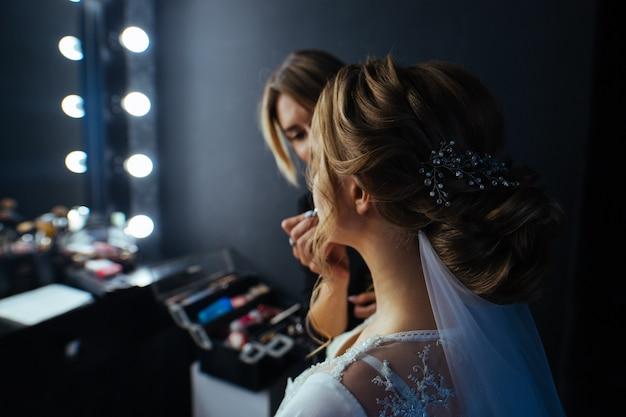 El artista de maquillaje pinta los labios para modelar con peinado. maquilladora hace hermosa novia maquillaje de novia delante del espejo con lámparas. concepto de belleza maquilladora profesional en el trabajo de cerca. Foto Premium