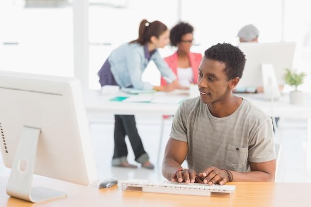 Artista masculino que usa la computadora con los colegas en fondo en la oficina Foto Premium
