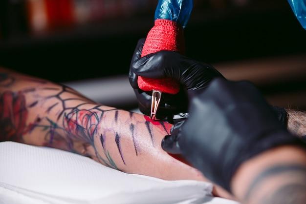 El artista profesional del tatuaje hace un tatuaje en la mano de una niña. Foto Premium