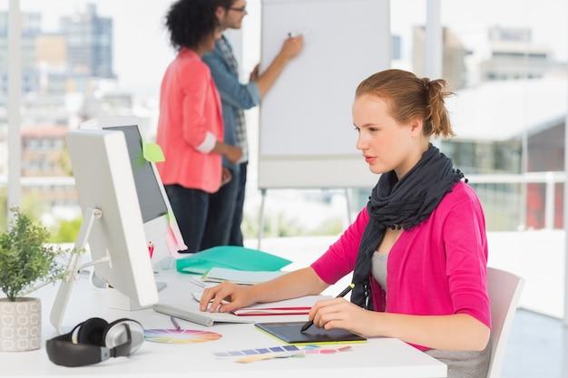 Artista de sexo femenino que usa la tableta gráfica con los colegas en la oficina Foto Premium