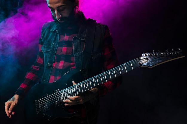 Artista tocando la guitarra y la luz del escenario violeta y humo. Foto gratis