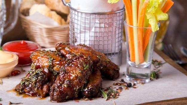 Ase las alitas de pollo en la bandeja de madera con las patatas fritas y las verduras. de cerca Foto Premium