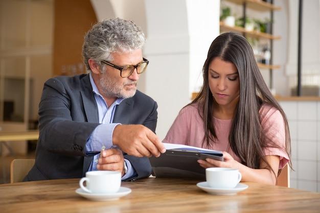 Asesor legal maduro que ayuda a los clientes jóvenes a completar el formulario del documento Foto gratis