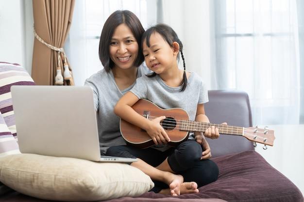 Asia madre e hija usando laptop y ukelele en casa Foto Premium