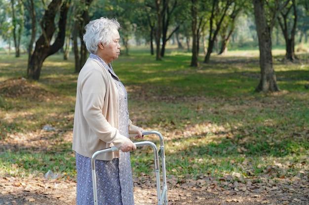 Asia paciente paciente caminar con caminante en el parque. Foto Premium