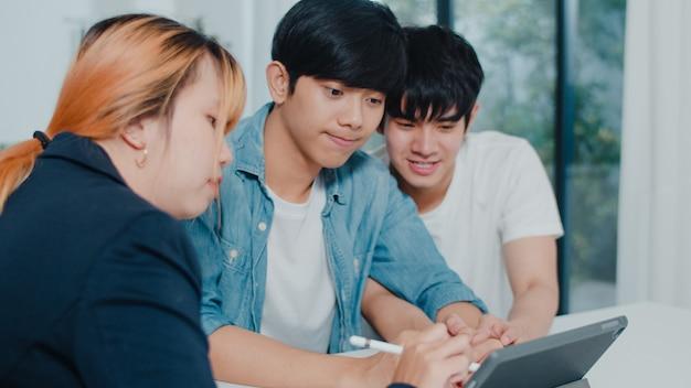 Asian gay lgbtq hombres pareja firman contrato en tableta en casa, pareja joven que consulta con asesor financiero inmobiliario, compra de casa nueva y apretón de manos con corredor en sala de estar en casa. Foto gratis