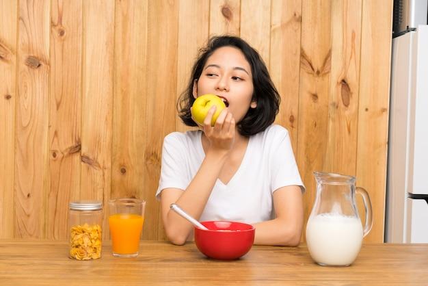 Asiática joven desayunando y con una manzana Foto Premium