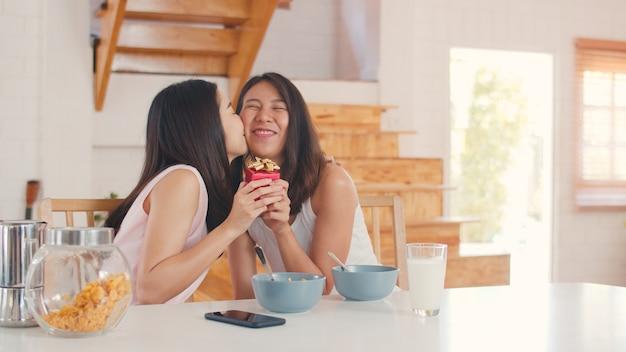 Asiático lesbianas lgbtq mujeres pareja dando presente hogar Foto gratis