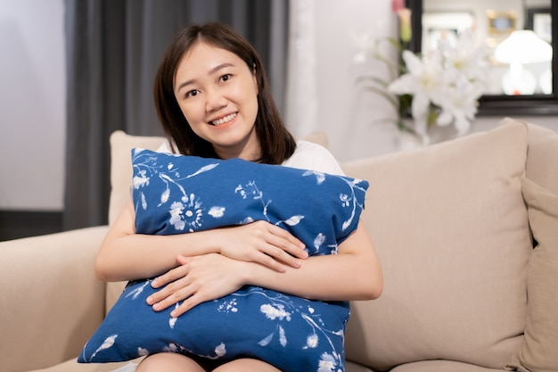 Los asiáticos se quedan y se relajan en la sala de estar y miran un televisor (tv) durante el período de cuarentena. Foto Premium