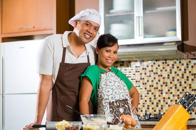 Asiatisches paar beim kuchen backen en küche Foto Premium