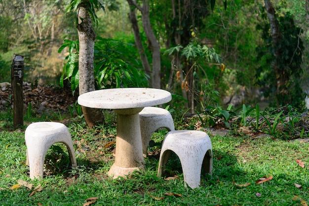 Asiento de jardín de piedra o mesa de piedra y bancos en el jardín. Foto Premium