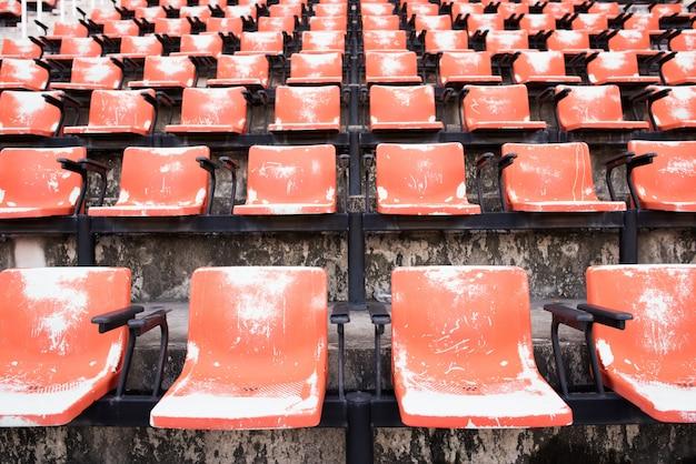 Asientos plásticos vacíos y viejos rojos en el estadio. Foto gratis