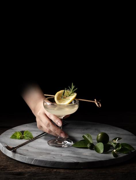 Asimiento de la mano de vidrio coctelera colador jigger sobre fondo de madera con espacio de copia Foto Premium