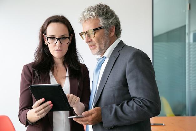 Asistente femenina morena mostrando datos al jefe y sosteniendo la tableta Foto gratis