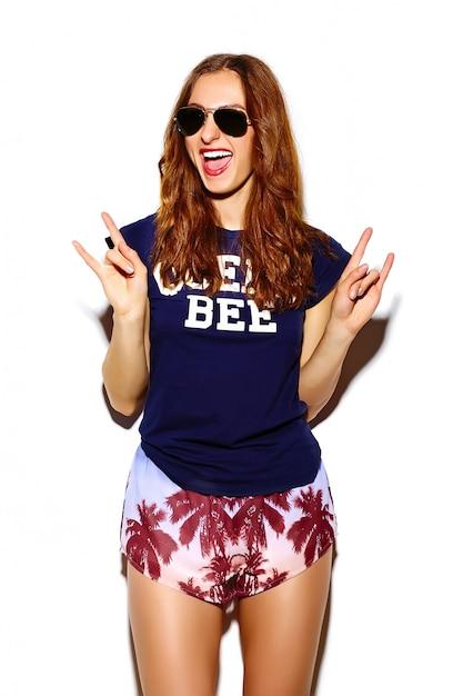 Aspecto de alta moda. gracioso glamour elegante sexy sonriente hermosa mujer joven modelo en verano brillante tela hipster muestra signo de rock and roll Foto gratis
