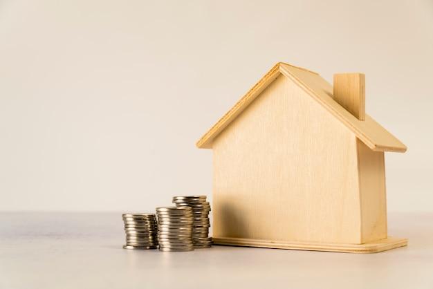 Astilla pila de monedas cerca de la casa de madera contra el fondo blanco Foto gratis