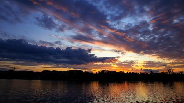 Atardecer en moldavia, exuberantes nubes con luz amarilla reflejada en la superficie del agua en primer plano Foto gratis