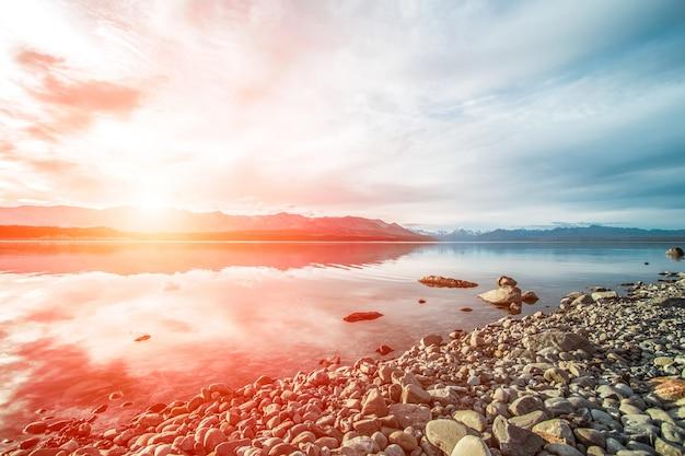 Atardecer en una playa de piedras Foto gratis