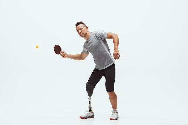 Atleta con discapacidad o amputado aislado en blanco. tenista profesional masculino con entrenamiento de prótesis de pierna Foto gratis