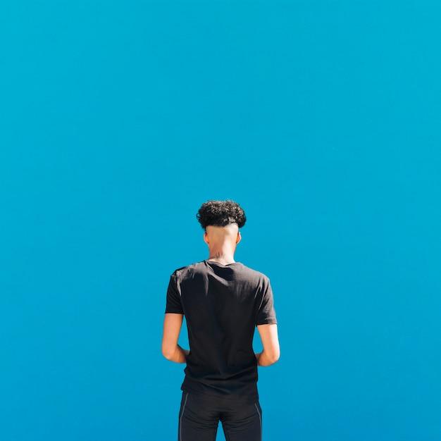 Atleta étnico en ropa deportiva negra sobre fondo azul Foto gratis