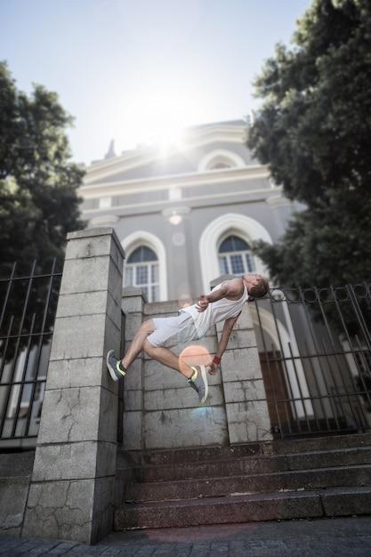 Atleta extremo que hace una voltereta hacia atrás delante de un edificio Foto Premium
