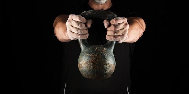 Atleta fuerte adulto en ropa negra sosteniendo un kettlebell de hierro Foto Premium