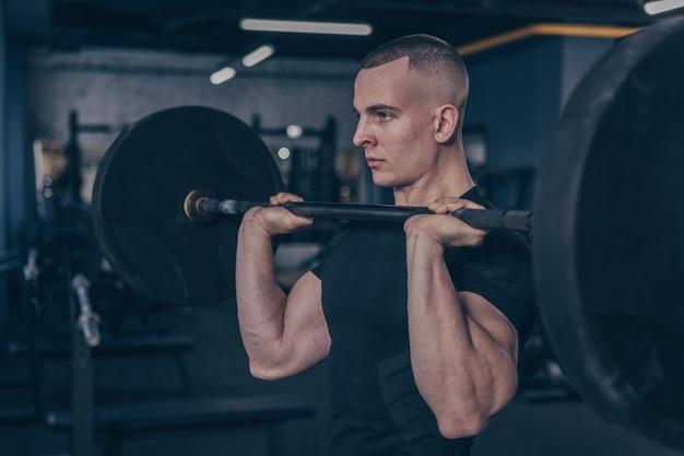 Atleta masculino musculoso trabajando con barra en el gimnasio studio Foto Premium