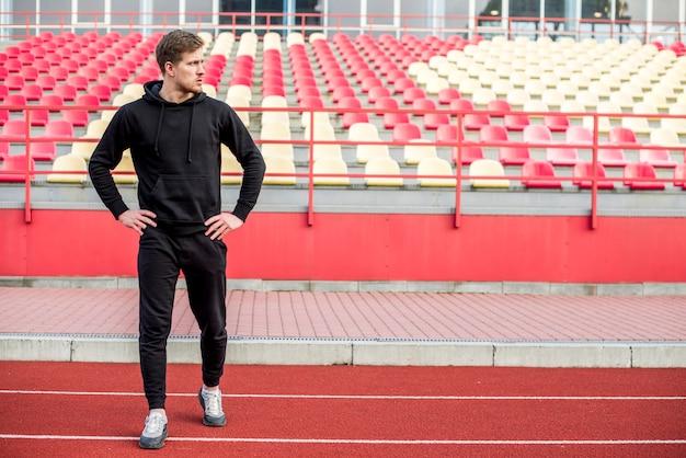 Un atleta masculino de pie delante de la grada haciendo ejercicio Foto gratis