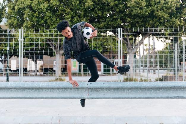 Atleta masculino en ropa deportiva saltando sobre barrera metálica Foto gratis