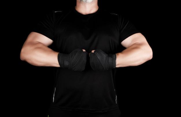 Atleta musculoso adulto en ropa negra con manos rebobinadas con una venda negra Foto Premium