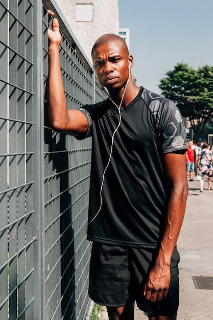 Atleta de sexo masculino africano joven serio con el auricular en sus oídos que se colocan delante de la puerta gris Foto gratis