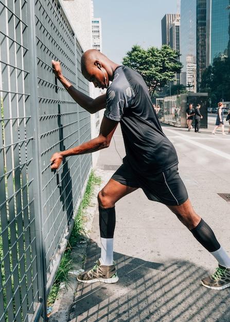 Atleta de sexo masculino joven africano que ejercita en al aire libre en ciudad Foto gratis