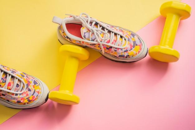 Atleta con zapatillas de deporte femeninas y pesas fondo amarillo-rosa. concepto de aptitud equipos para gimnasio y hogar. Foto Premium