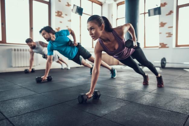 Atletas en el piso. levantamiento de pesas con una mano Foto Premium