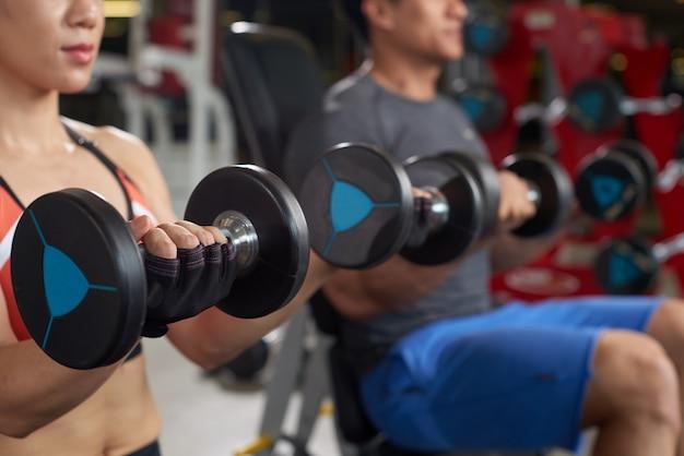 Atletas recortados haciendo ejercicio en un día de brazos en un gimnasio Foto gratis