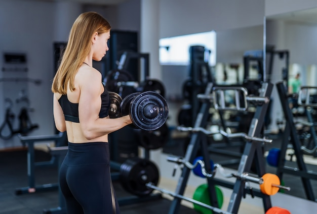 Atlética mujer de pelo largo bombeo de musculatura con pesas frente al espejo en el gimnasio. Foto Premium