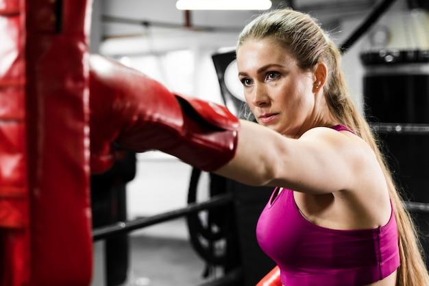 Atlética mujer rubia recibiendo ayuda en el entrenamiento Foto gratis