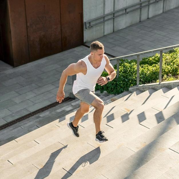 Atlético hombre corriendo en las escaleras al aire libre Foto gratis