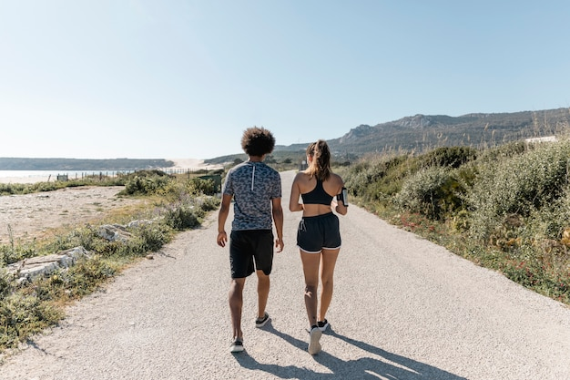 Atlético hombre y mujer caminando por la carretera Foto gratis