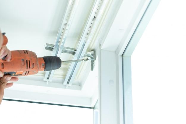 Atornille los tornillos para instalar las cortinas por técnicos profesionales. Foto Premium