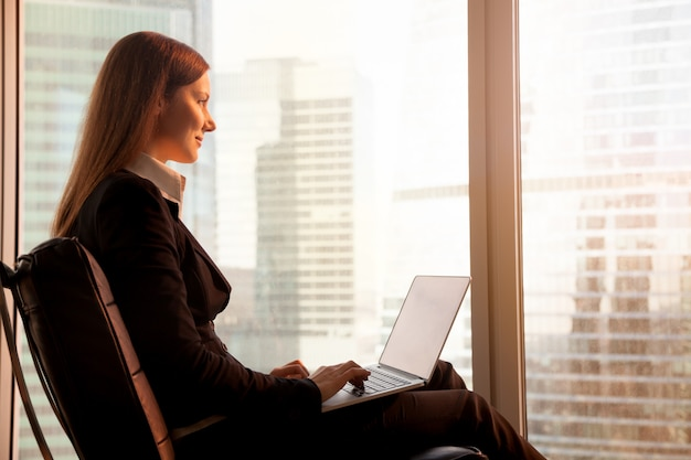Atractiva empresaria disfrutando del atardecer, relajándose en la oficina cha Foto gratis